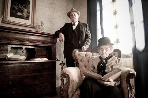 coppia di anziani con eleganti vestiti d'epoca in salotto, lui in piedi mentre lei seduta legge