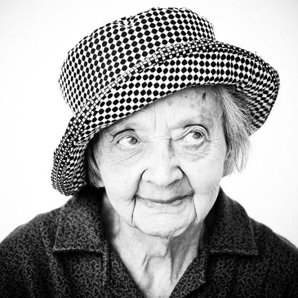 primo piano di signora anziana con cappello, sorridente guarda lateralmente in alto