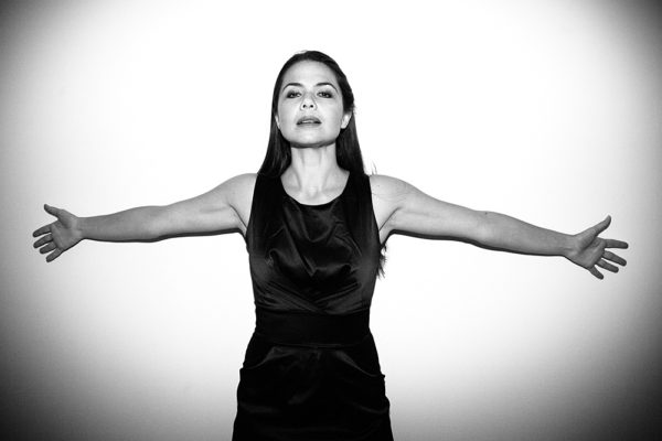 donna a braccia aperte contro muro bianco