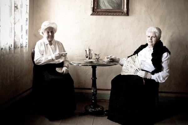 coppia di signore anziane con eleganti vestiti d'epoca bevono il te sedute ad un tavolino
