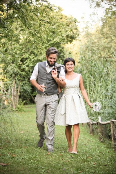 ritratto fotografico nozze sposi camminano sorridenti bicchiere vino bouquet sentiero provincia vicenza