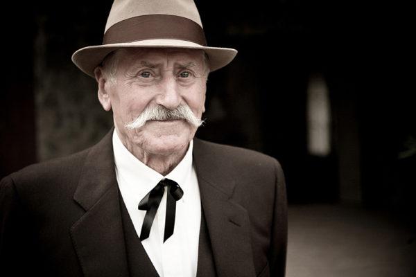 anziano con baffi bianchi, cappello e vestito elegante