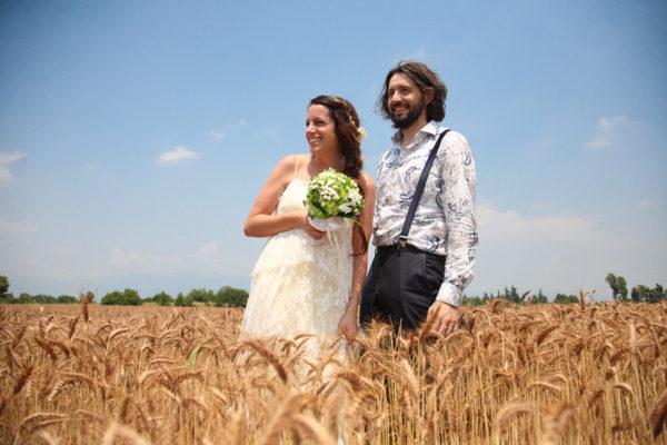 servizio fotografico matrimonio vicenza sposi sorridono guardando orizzonte campo grano ripresi basso fotografo