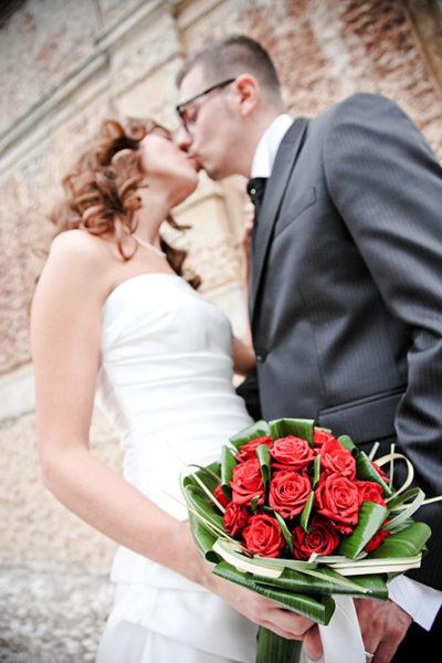fotografo-matrimonio-bacio-sposi-bouquet-rose-rosse