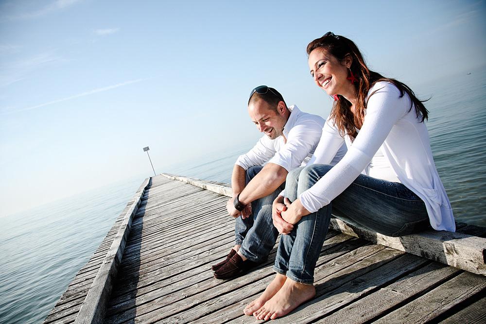 coppia sorridente seduta sul bordo di un pontile sul mare