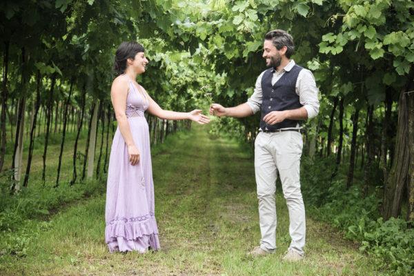 fotografo shooting prematrimoniale uomo porge fiori campo ragazza sotto vigne colli berici