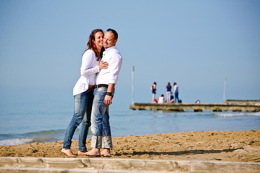 coppia in spiaggia sorride e si abbraccia, in jeans e camicia bianca, vicina a pontile