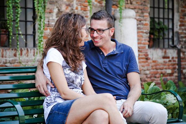 coppia sorridente si guarda seduti su una panchina