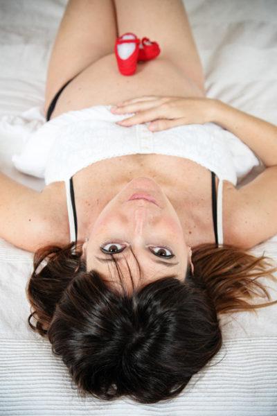 donna in gravidanza guarda il fotografo stesa sul letto con le scarpine del bambino appoggiate sulla pancia