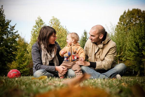 fotografo famiglia vicenza genitori mamma papà bambina bambina seduti parco prato