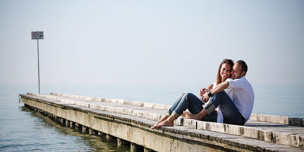 ragazzo tiene abbracciata da dietro ragazza. ridono seduti su pontile sul mare