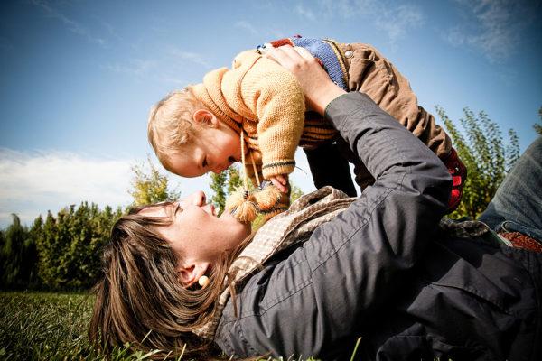 fotografo famiglia vicenza mamma prato solleva figlia gioco