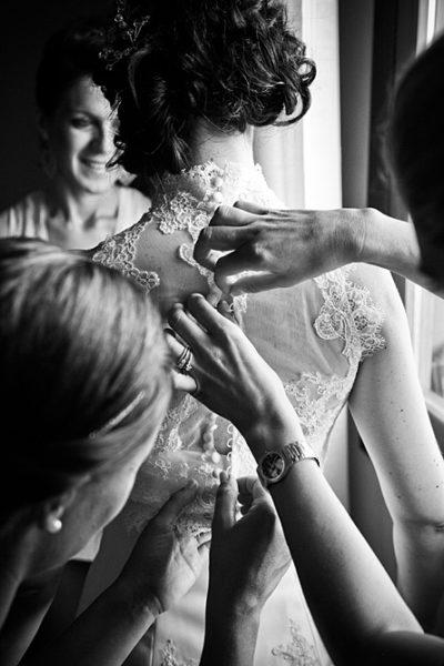 fotografo-nozze-vestizione-sposa-mani-bottoni-vestito-vicenza