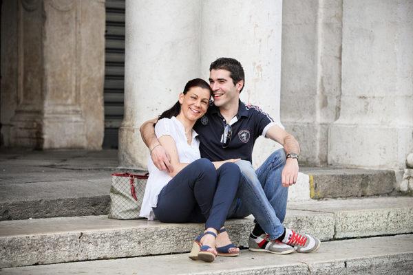 coppia abbracciata sorride seduta sugli scalini sotto la basilica palladiana a vicenza