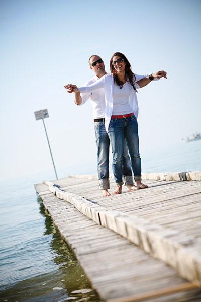 ragazzo tiene sollevate le braccia di una ragazza sorridente, da dietro, su pontile in spiaggia
