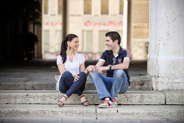 coppia seduta si sorride seduta sugli scalini sotto la basilica palladiana a vicenza