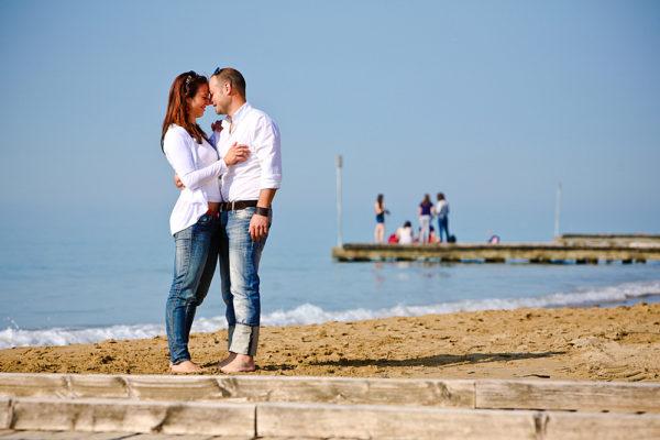 coppia abbracciata in spiaggia , vicino a pontile